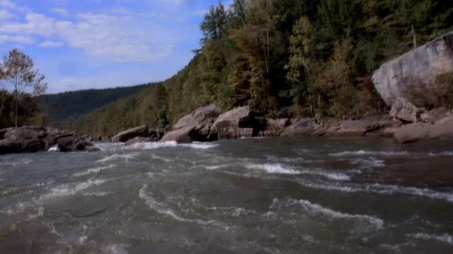 Wide shot White water rapids splashing along riverbank/ British Columbia, Canada