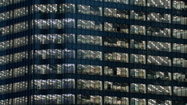 wide shot windows of office building at night with visible people inside/ london - rectangle stock videos & royalty-free footage