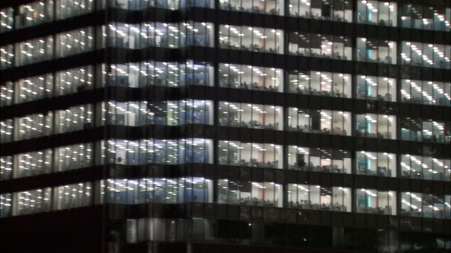 wide shot windows of office building at night/ zoom in medium shot with visible people inside/ london - nicht erkennbare person stock-videos und b-roll-filmmaterial