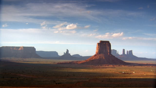 """vidéos et rushes de wide shot wispy clouds in blue sky over """"the mittens"""" in monument valley / utah - piton rocheux"""