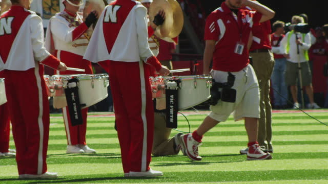 Wide shot with crowd of spectators in a stadium as the marching band drum percussion section marches and performs during half time at a football game.