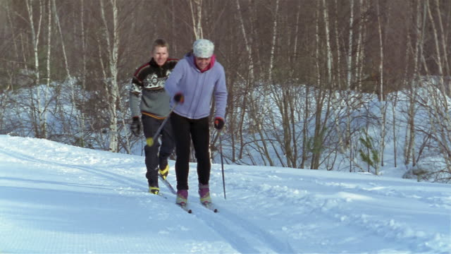 wide shot woman and man cross-country skiing - skijacke stock-videos und b-roll-filmmaterial