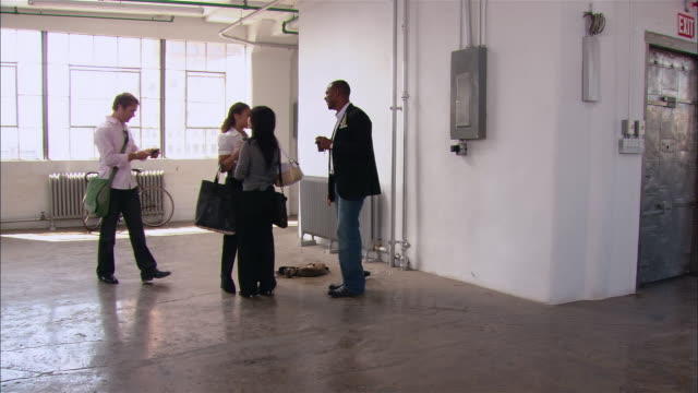 wide shot woman arriving for meeting with three others in empty loft space/ may taking picture of business partners wtih camera phone/ brooklyn, new york - casual clothing stock-videos und b-roll-filmmaterial