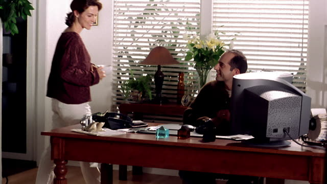 wide shot woman bringing coffee to man working on computer at desk and hugging him - arbeitszimmer stock-videos und b-roll-filmmaterial