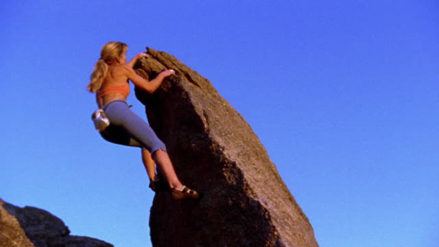 wide shot woman climbing rock / new mexico - lachaos stock videos & royalty-free footage