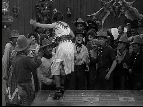 1915 B/W Wide shot Woman dancing on table in front of crowd of cowboys in saloon