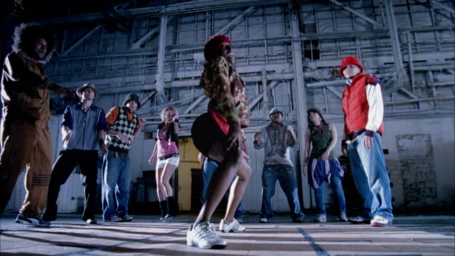 Wide shot woman dancing suggestively in warehouse as people watch