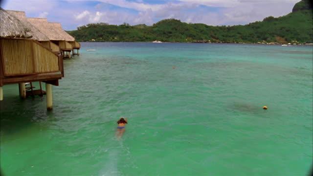 wide shot woman diving into water / swimming past row of huts / bora boar - bikinihose stock-videos und b-roll-filmmaterial