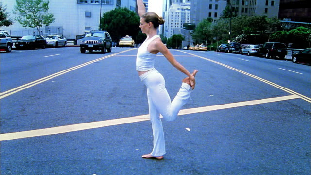 Wide shot woman doing yoga (balancing on one leg) on city street / Los Angeles