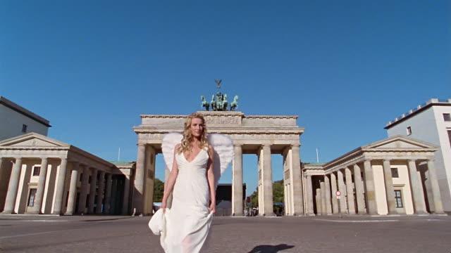 wide shot woman dressed as angel walking in front of brandenburger gate / berlin, germany - dejaover点の映像素材/bロール