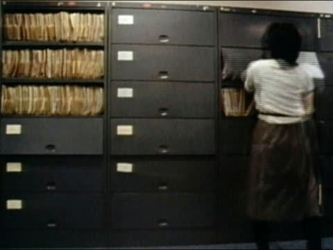 1984 wide shot woman filing in room of floor-to-ceiling file cabinets / fast motion / AUDIO