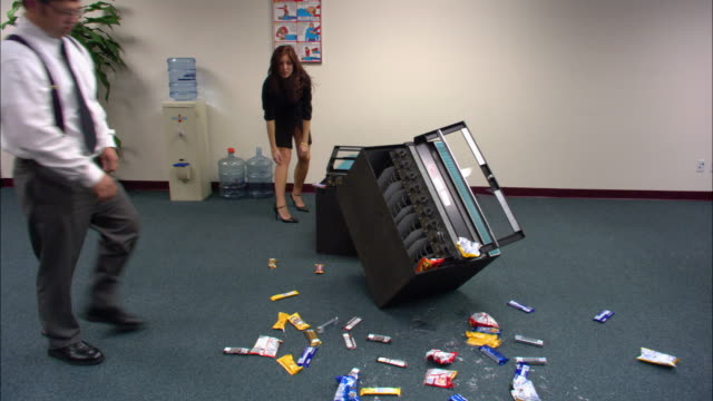 vidéos et rushes de wide shot woman hunching over knocked down vending machine / man picking up spilled snack / low angle - distressed