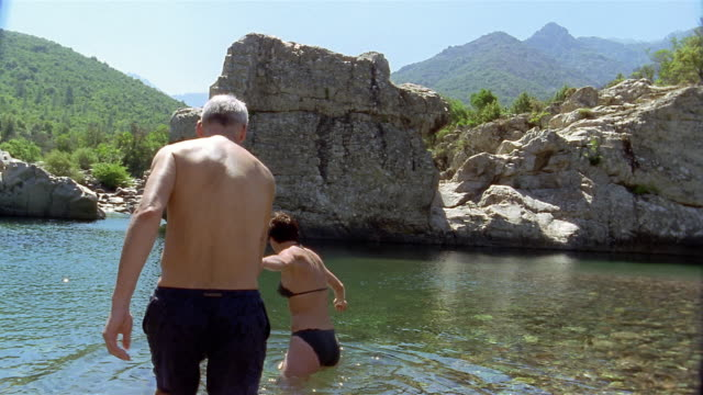 wide shot woman in bikini leading man by the hand into water / corsica - swimwear stock videos and b-roll footage