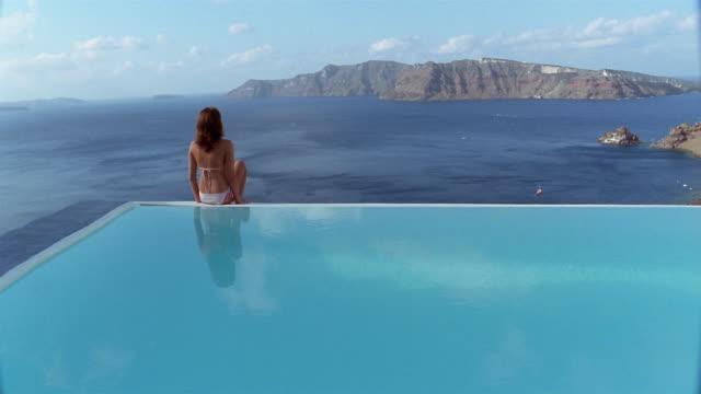 Wide shot woman in bikini sitting on edge of infinity pool and looking at Aegean / Santorini, Greece