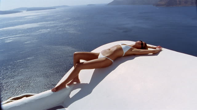 Wide shot woman in bikini sunbathing on terrace with view of Aegean Sea / sitting up / Santorini, Greece