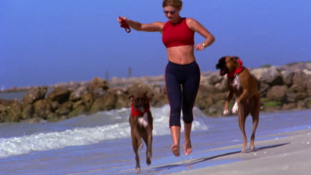 Wide shot woman in exercise outfit running on beach with two dogs (boxers) / Florida