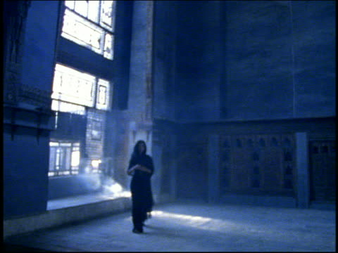 Wide shot woman in hooded robe standing by window in Arab palace and walking toward camera / Cairo, Egypt