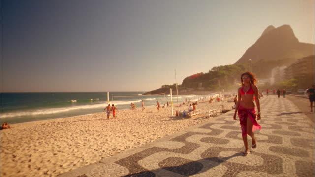 vídeos y material grabado en eventos de stock de wide shot woman in sunglasses walking past cam on beach boardwalk / volleyball players in background / rio - sólo mujeres jóvenes