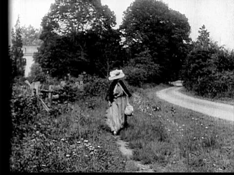 1910 B/W Wide shot woman in wide straw hat walking on side of country road