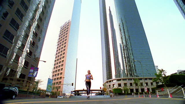 wide shot woman jogging towards and over camera on city street / los angeles - spandex stock videos & royalty-free footage
