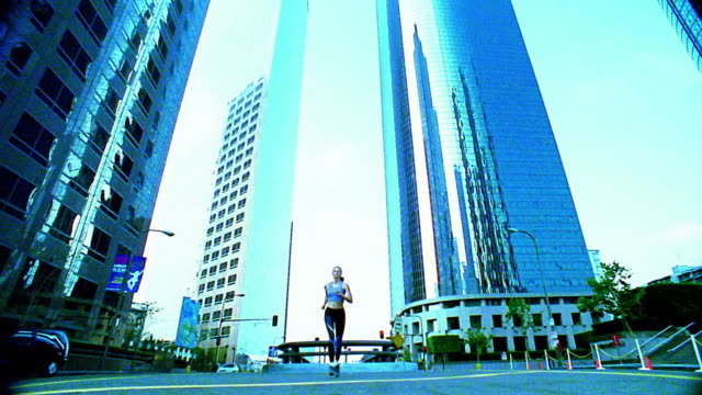 stockvideo's en b-roll-footage met wide shot woman jogging towards and over camera on city street / los angeles - elasthaan