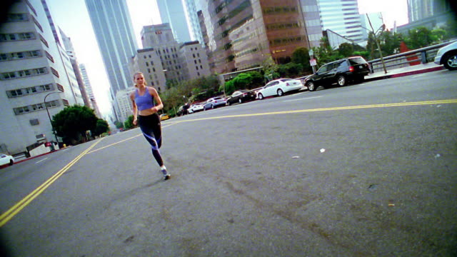 wide shot woman jogging towards and past camera on city street / los angeles - spandex stock videos & royalty-free footage
