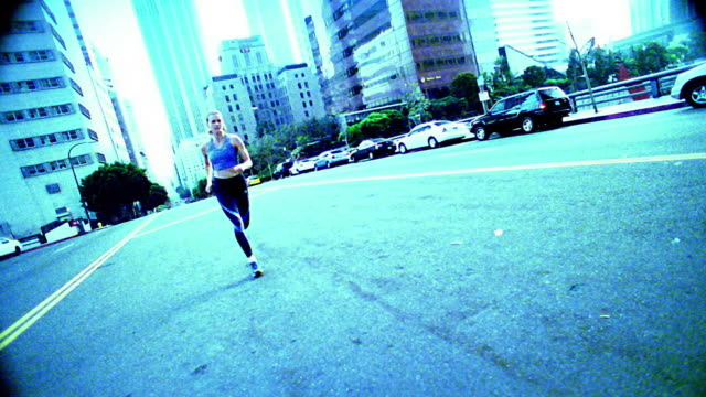 stockvideo's en b-roll-footage met wide shot woman jogging towards and past camera on city street / los angeles - elasthaan