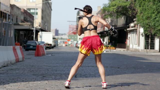 vídeos de stock, filmes e b-roll de wide shot woman kickboxing in street/ manhattan, new york, usa - sutiã para esportes