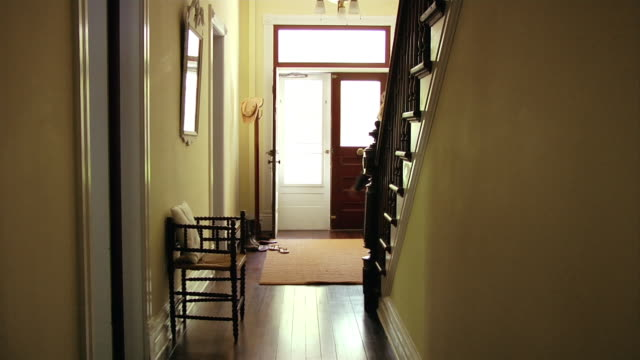 wide shot woman leaving hallway out front door of house/ roxbury, new york - ドア点の映像素材/bロール