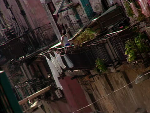 2003 wide shot woman on balcony hanging laundry on clothesline over street / cuba - hanging stock videos & royalty-free footage