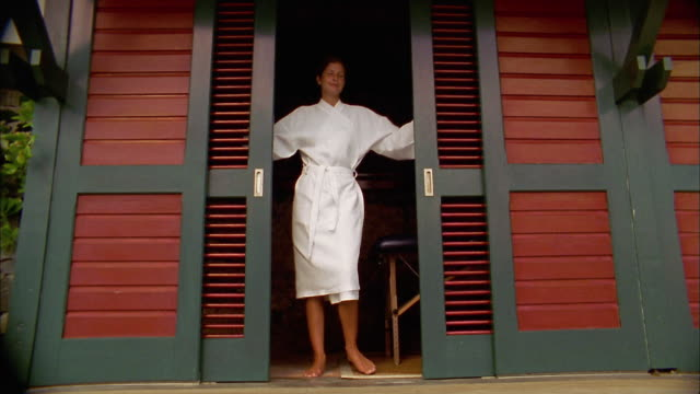 wide shot woman opening sliding doors and exiting - bathrobe stock videos & royalty-free footage