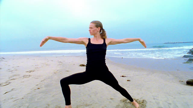 "vídeos de stock e filmes b-roll de wide shot woman performing ""warrior"" and ""triangle"" yoga poses on beach / los angeles - body de ginástica"