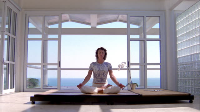 wide shot woman performing yoga and sitting w/eyes closed in 'lotus' position w/sky + water in background - lotus position stock videos & royalty-free footage
