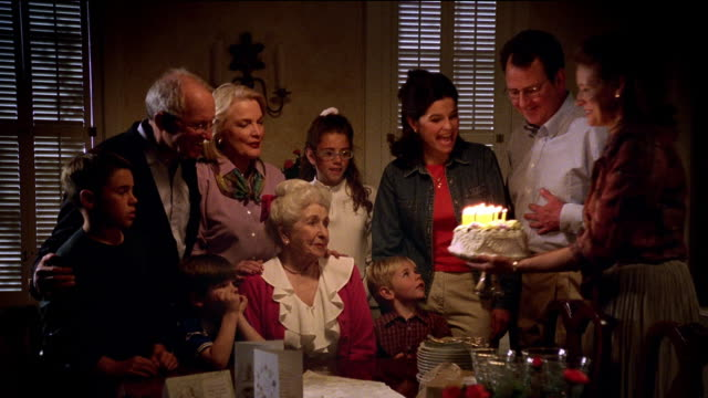 wide shot woman putting birthday cake in front of senior woman at family birthday party with gifts in foreground - großmutter stock-videos und b-roll-filmmaterial