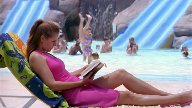 stockvideo's en b-roll-footage met wide shot woman reading book on beach chair at water park / waving to young girls in pool in background - waterpark