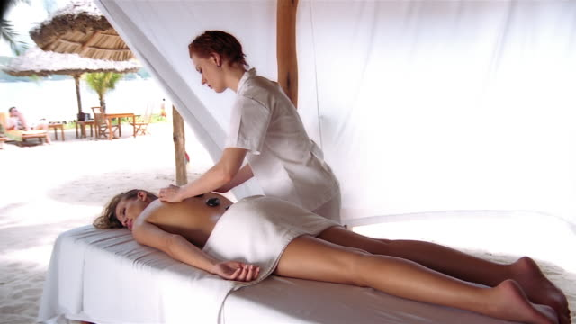 wide shot woman receiving hot stone massage from masseuse - massage table stock-videos und b-roll-filmmaterial
