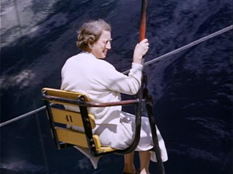 1951 wide shot woman riding ski lift in banff national park / banff, alberta, canada  - amateurfilm stock-videos und b-roll-filmmaterial