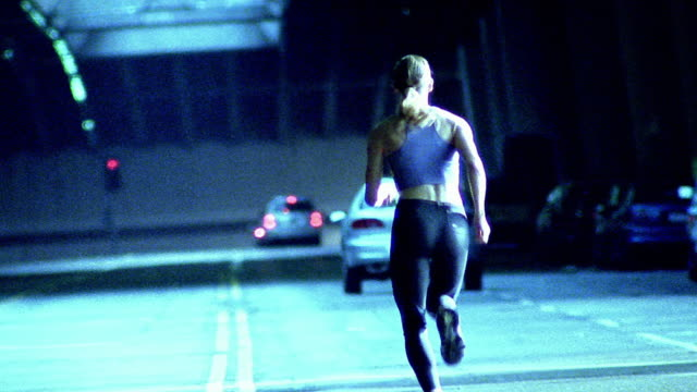stockvideo's en b-roll-footage met wide shot woman running away from camera on city street / los angeles - elasthaan