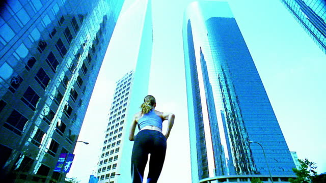 wide shot woman running over and away from camera on city street / los angeles - spandex stock videos & royalty-free footage