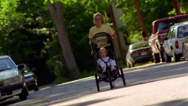 CANTED wide shot woman running with female toddler in exercise stroller on suburban street