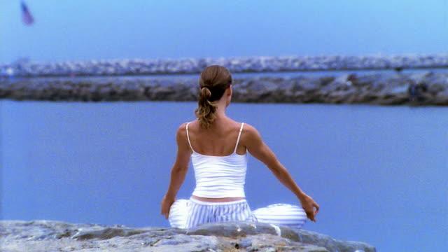 wide shot woman sitting cross-legged doing yoga next to water / los angeles - woman cross legged stock videos & royalty-free footage