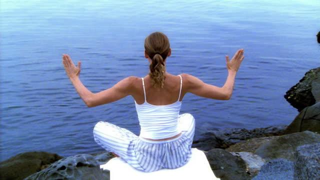 wide shot woman sitting cross-legged doing yoga on rocks next to water / los angeles - woman cross legged stock videos & royalty-free footage