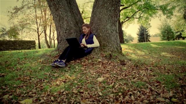 Wide shot woman sitting under tree typing on laptop/ Solebury, Pennsylvania