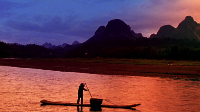 wide shot woman standing and rowing boat on river with mountains in background / li river, china - li river stock videos & royalty-free footage