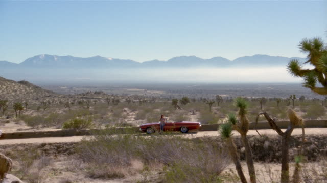 wide shot woman standing by convertible on desert road - stranded stock videos and b-roll footage