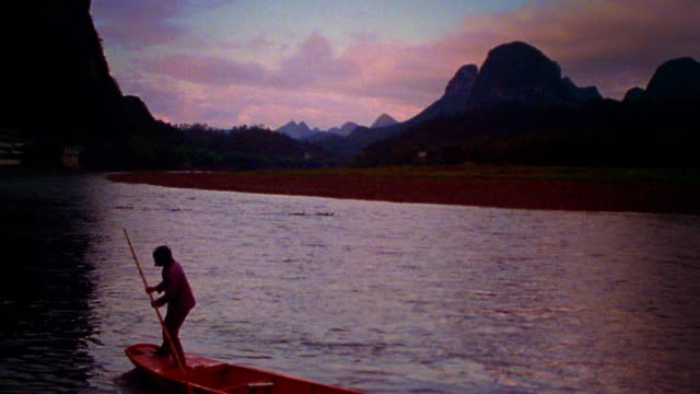 wide shot woman standing on bow of riverboat and steering on li river with mountains in background / china - li river stock videos & royalty-free footage