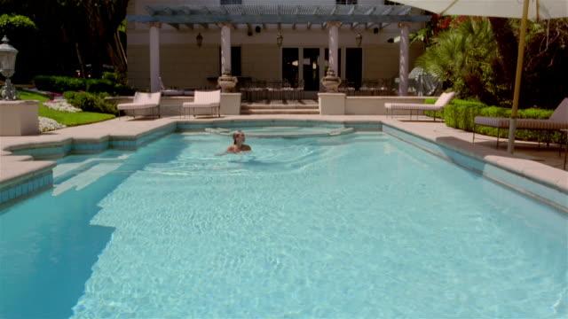 stockvideo's en b-roll-footage met wide shot woman swimming in pool towards camera - buitenbad