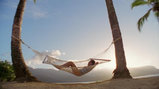 wide shot woman swinging in hammock - auf dem rücken liegen stock-videos und b-roll-filmmaterial