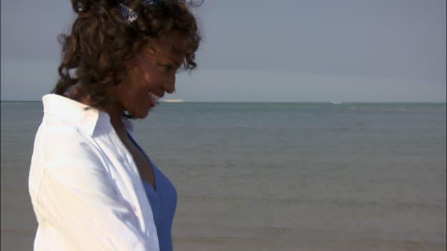 stockvideo's en b-roll-footage met wide shot woman wading barefoot in surf on beach / miami, florida, usa - hemden en shirts