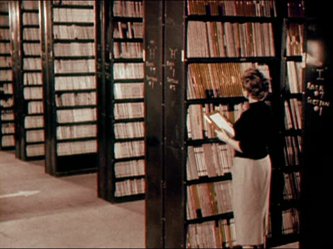 1956 wide shot woman walking and holding record/ woman filing record on shelf in large library/ audio - bibliotecario video stock e b–roll